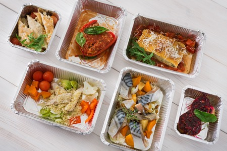 low carb diet: Healthy food delivery, daily ration. Take away of natural organic low carb diet. Fitness nutrition in foil boxes. Top view, flat lay with copy space at white wood. Mackerel fish, vegetables and fruits Stock Photo