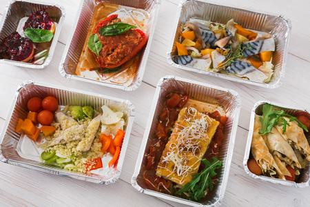 low carb diet: Healthy food delivery, daily ration. Take away of natural organic low carb diet. Fitness nutrition in foil boxes. Top view, flat lay with copy space at white wood. Lasagna, vegetables and fruits