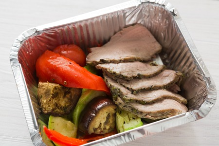carb: Healthy food delivery or take away, diet concept. Organic nutrition with protein, carb and fat balance. Weight loss dish in foil box. Baked vegetables and steamed veal.