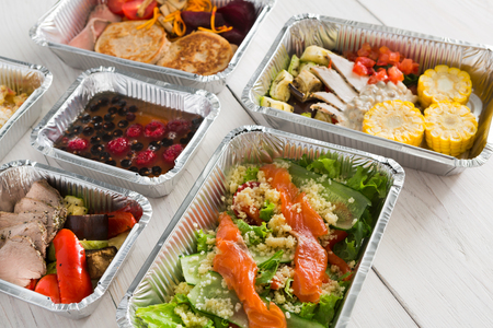 ration: Healthy food delivery, daily ration. Take away of natural organic low carb diet of vegetables, fish and meat. Fitness nutrition in foil boxes on white wood background