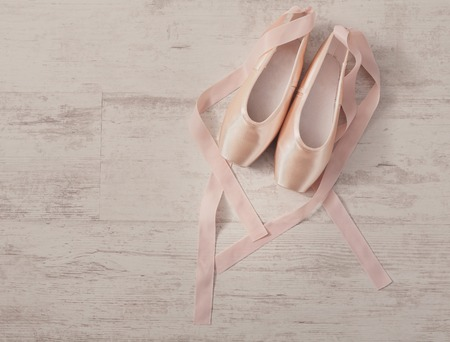 pointe shoes: Pastel pink ballet shoes background. New pointe shoes with satin ribbon lay on white rustic shubby chic wood, top view with copy space