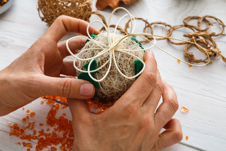 Creative diy craft hobby. Making handmade craft christmas ornaments and balls with felt spruce tree. Womans leisure, holiday decorations. Closeup of female hands at white wood background