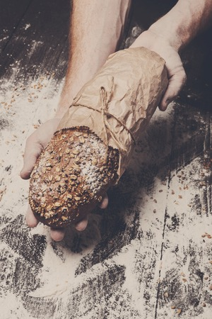 carefully: Warm fresh rye whole grain bread, wrapped in craft paper. Healthy baking and cooking concept background. Hands carefully hold loaf on wooden table background, sprinkled with flour. Soft toning