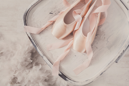 pointe shoes: Pastel pink ballet shoes background. New pointe shoes with satin ribbon lay on white rustic shubby chic chair near feather boa, top view from above