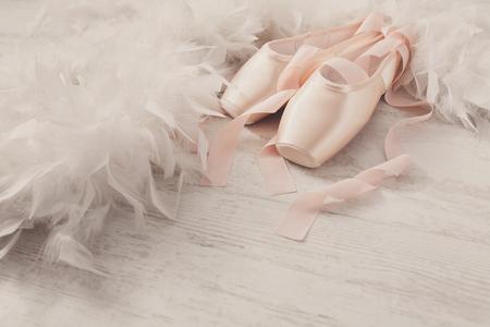 Pastellrosa Ballettschuhe Hintergrund. New pointe Schuhe mit Satinband lag auf weiß rustikal Shubby chic Holz in der Nähe von Federboa, Ansicht mit Kopie Raum