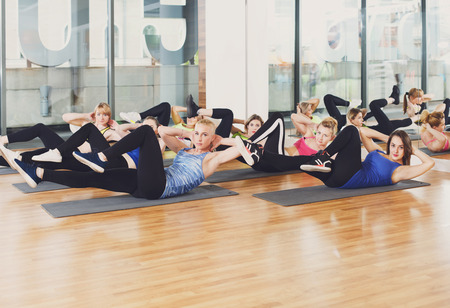 Group of young women in fitness club making exercises. Girls do cross crunches for abs. Healthy lifestyle at training in aerobics studio.