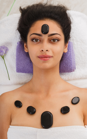 warming therapy: Black marble stone massage in spa. Beautiful girl in wellness center. Professional relaxation procedure to attractive young indian girl in beauty parlor, top view