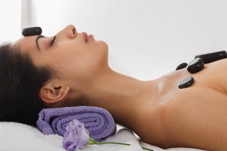 warming therapy: Black marble stone massage in spa. Beautiful girl in wellness center. Professional relaxation procedure to attractive young indian girl in beauty parlor.