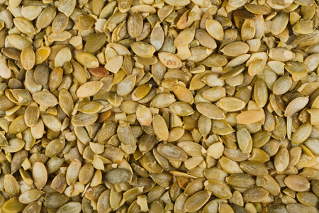 low fat: Pile of peeled skinless pumpkin seeds close-up as abstract food background. Lots of healthy vegan and vegetarian food, rich of energy low fat nutrition