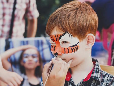 animateur de l'enfant, la main de l'artiste dessine la peinture de visage pour petit garçon. Enfant avec la peinture drôle de visage. Painter fait les yeux de tigre sur le visage de garçon. Enfants vacances, événement, fête d'anniversaire, de divertissement.