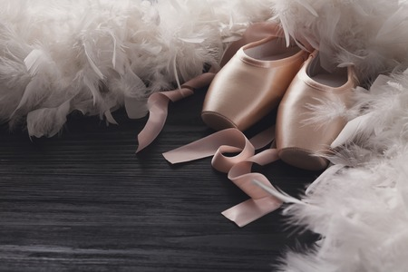 pointe shoes: Pastel pink ballet shoes background. New pointe shoes with satin ribbon lay on black rustic shubby chic wood near feather boa, view with copy space Stock Photo