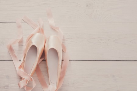 pointe shoes: Pastel pink ballet shoes background. New pointe shoes with satin ribbon lay on white rustic shubby chic wood, top view with copy space, soft toning
