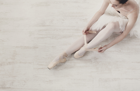 pointe shoes: Beautiful legs of young ballerina who puts on pointe shoes at white wooden floor background, top view from above with copy space. Ballet practice. Beautiful slim graceful feet of ballet dancer.