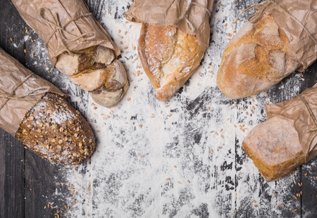sorts: Baking and cooking concept background. Lots of different bread sorts, wrapped in craft paper top view with copy space in the middle on wooden table, sprinkled with flour. Stock Photo
