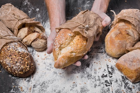 carefully: Lots of different bread sorts, wrapped in craft paper. Baking and cooking concept background. Hands of baker carefully hold loaf on wooden table, sprinkled with flour.