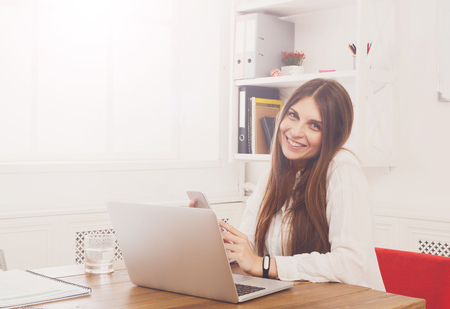 carreer: Beautiful young businesswoman sitting by wooden desk with laptop. Modern office worker in white room interior. Succesfull woman, female carreer concept. Stock Photo