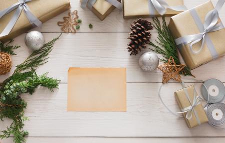 Kreative DIY Hobby Hintergrund. Handgemachte machen Weihnachtsgeschenk, Box in Handwerk Papier mit Satinsilber Band. Draufsicht auf weißen Holztisch mit Kopie Platz auf Blatt Papier, Dekoration von Geschenk. Lizenzfreie Bilder