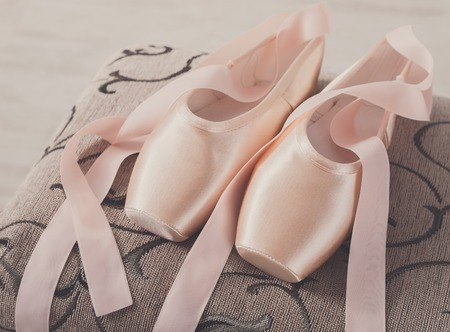 pointe shoes: Pastel pink ballet shoes background. New pointe shoes with satin ribbon lay on chair