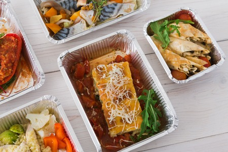 ration: Healthy food delivery, daily ration. Take away of natural organic low carb diet. Fitness nutrition in foil boxes. Top view, flat lay with copy space at white wood. Lasagna, vegetables and fruits