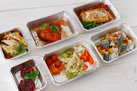 ration: Healthy food delivery, daily ration. Take away of natural organic diet. Fitness nutrition in foil boxes on white wood. Lasagna, vegetables, fish and fruits. Carbs, protein, fat balanced diet
