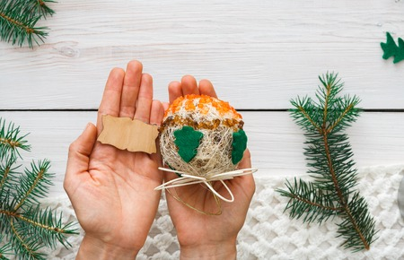 lable: Creative diy craft hobby. Woman shows craft christmas ball with felt spruce tree and empty wooden lable with copy space. Home leisure, holiday decorations. Closeup of female hands at wood background