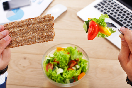 hand lay: Business lunch at working place. Businessman in office. Healthy, diet food, vegetable salad with apple and juice. Cell phone, laptop and papers, fitness bracelet on hand. Top view, flat lay Stock Photo