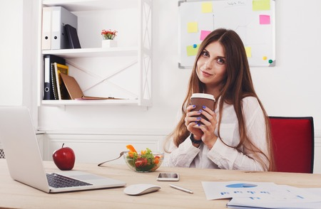 healthy snack: Woman has healthy business lunch in modern office interior. Young beautiful businesswoman at working place, eats vegetable salad in bowl, enjoys her coffee take away. Diet and vegetarian concept.