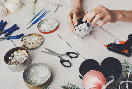 Creative diy hobby. Making handmade craft black stylish christmas balls with lace. Womans leisure, tools for creating holiday decorations. Female hands closeup working on white wooden table
