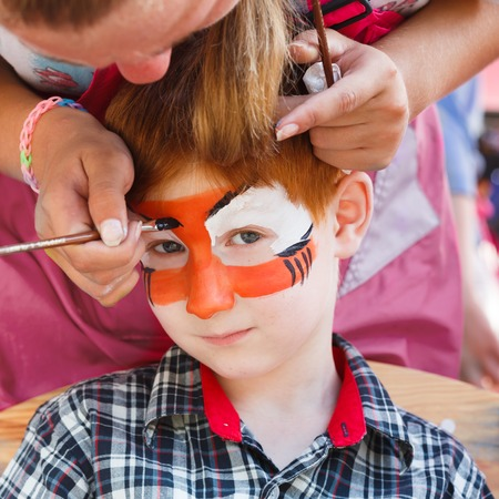 tiger eyes: Child animator, artists hand draws face painting to little boy. Child with funny face art. Painter makes tiger eyes on boys face. Children holiday, event, birthday party, entertainment.