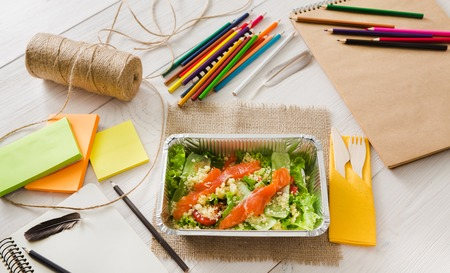 eat right: Healthy lunch of artist. Diet concept. Take away food in foil boxes, papers and pencils on working table of creative person or art student. Salmon salad, top view on white wood Stock Photo