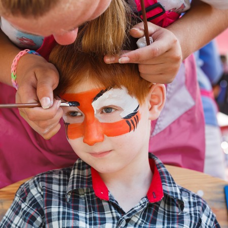 tiger eyes: Artists hand draws face painting to little boy. Child with funny face art. Painter makes tiger eyes on boys face. Children holiday, event, birthday party, entertainment.