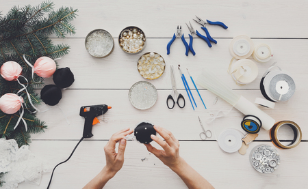 Creative diy hobby. Making handmade craft christmas balls. Womans leisure, tools for creating holiday decorations, pliers, glue gun and scissors. Top view of white wooden table with female hands.