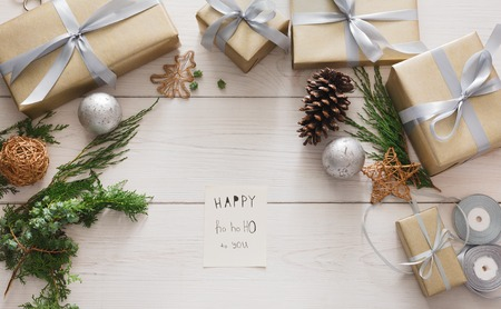 Wrapping gifts background. Handmade making christmas present, box in craft paper with satin silver ribbon. Top view of white wooden table with congrats on sheet of paper, decoration of gift.