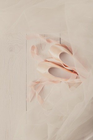 pointe shoes: Pastel pink ballet shoes background. New pointe shoes with satin ribbon and chiffon tutu lay on white rustic shubby chic wood, top view with copy space, vertical image
