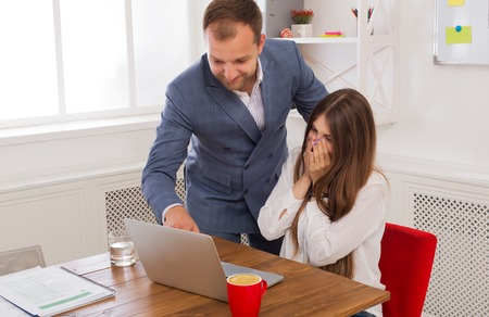 Businessman supervising his assistants work on the laptop computer. Man helps woman in the office. Male boss and female secretary. Communication of manager and stuff, checking job execution Stock Photo