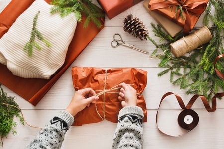 pinecones: Gift wrapping background. Female hands packaging sweater as christmas present in maroon paper decorated with satin ribbon. Winter holidays concept. Top view of white wood table with fir tree branches Stock Photo
