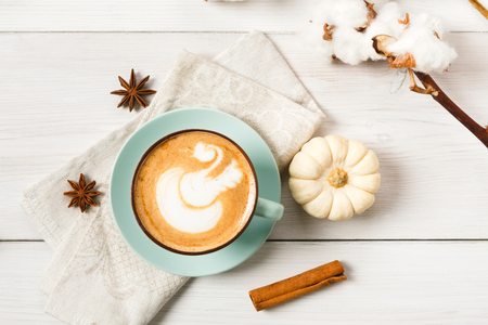 Pumpkin spice latte. Blue coffee cup with creamy foam, cinnamon sticks, cloves and small yellow pumpkins at white wood background. Autumn fall hot drinks, cafe and bar concept, top view Banco de Imagens