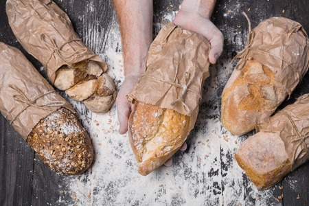 sorts: Lots of different bread sorts, wrapped in craft paper. Baking and cooking concept background. Hands of baker carefully hold loaf on wooden table, sprinkled with flour.