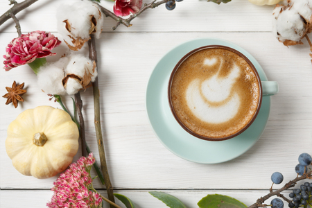 Pumpkin spice latte. Blue coffee cup with foam, cinnamon sticks, autumn flowers and small yellow pumpkins at white wood background. Fall hot drinks, cafe and bar concept, top view