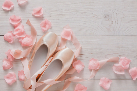 pointe shoes: Pastel pink ballet shoes background. New pointe shoes with satin ribbon and rose petals lay on white rustic shubby chic wood, top view with copy space, soft toning