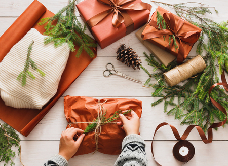 female christmas: Gift wrapping background. Female hands packaging sweater as christmas present in maroon paper decorated with satin ribbon. Winter holidays concept. Top view of white wood table with fir tree branches Stock Photo