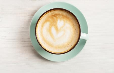Cappuccino's met schuimend schuim, blauwe close-upclose-up van de koffiekop op witte houten achtergrond. Café en bar, barista-kunstconcept.
