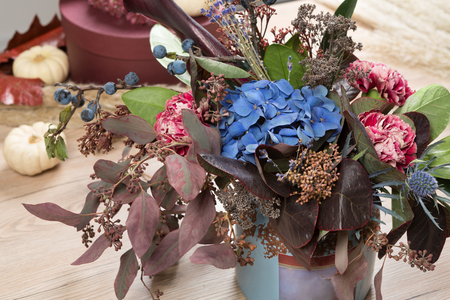 Beautiful autumn bouquet composition of dried roses and meadow flowers with leaves, floral fall background. Floristic art decoration closeup.