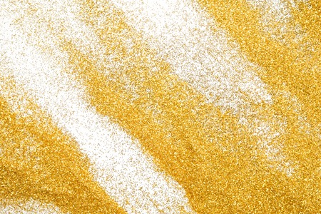 shimmer: Golden glitter sand texture on white, abstract background. Yellow dusty shimmer decoration, shiny and sparkling. Holidays and glamour concept. Stock Photo