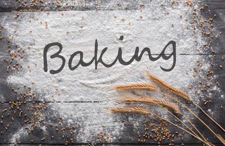 Baking class or recipe concept on dark background, sprinkled wheat flour, grain and ears with text at copy space. Top view on wooden board or table. Cooking dough or pastry. Stock Photo