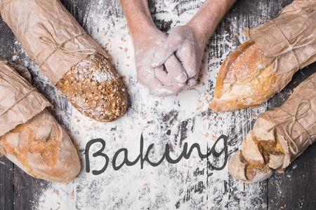 sorts: Bread making. Lots of different bread sorts, wrapped in craft paper. Baking and cooking concept background. Hardworking hands of baker on wooden table, sprinkled with flour.