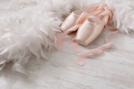 pointe shoes: Pastel pink ballet shoes background. New pointe shoes with satin ribbon lay on white rustic shubby chic wood near feather boa, view with copy space