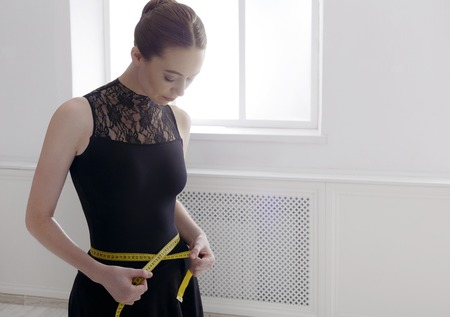 cintura perfecta: Ballet dancer looks at her perfect waist after diet. Beautiful graceful ballerine in black with measuring tape in light hall. Slimming and weight loss concept, copy space Foto de archivo