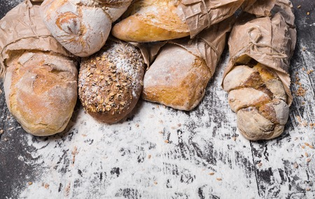 sorts: Baking and cooking concept background. Border of different bread sorts, wrapped in craft paper top view with copy space on wooden table, sprinkled with flour.