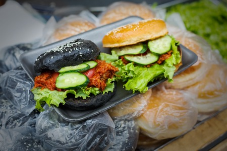 Fresh burgers on grill. Cookout bbq food. Unusual black and white hamburger with roasted onion, meat and vegetables filling closeup. Vendor street fast food.